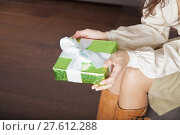 Купить «holding green gift on parquet background», фото № 27612288, снято 20 февраля 2019 г. (c) PantherMedia / Фотобанк Лори