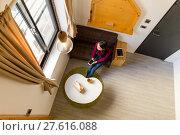 Купить «Top view of woman holding a cellphone and look at the window», фото № 27616088, снято 20 февраля 2019 г. (c) PantherMedia / Фотобанк Лори