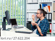 Купить «man is working in his office and eating granola», фото № 27622204, снято 1 апреля 2020 г. (c) PantherMedia / Фотобанк Лори
