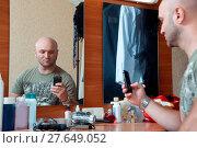 Man photographs herself in the mirror. Стоковое фото, фотограф Zoonar/Artem Merzlen / easy Fotostock / Фотобанк Лори