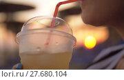 Купить «Woman enjoying iced drink outdoor at sunset», видеоролик № 27680104, снято 10 декабря 2018 г. (c) Данил Руденко / Фотобанк Лори