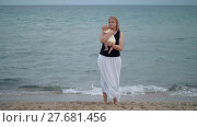 Mother with lost look holding baby being alone at the beach near sea. Стоковое видео, видеограф Данил Руденко / Фотобанк Лори