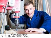 Купить «portrait of man in uniform working with electrical screwdriver on plywood indoors», фото № 27686732, снято 19 января 2019 г. (c) Яков Филимонов / Фотобанк Лори