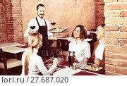 Купить «Male waiter bringing order to visitors», фото № 27687020, снято 22 июля 2018 г. (c) Яков Филимонов / Фотобанк Лори