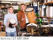 Купить «Father and teenage son examining drum units in guitar shop», фото № 27687064, снято 29 марта 2017 г. (c) Яков Филимонов / Фотобанк Лори