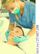 Купить «Female doctor is doing massage of skin of face to client», фото № 27687248, снято 20 февраля 2019 г. (c) Яков Филимонов / Фотобанк Лори