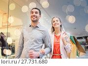 Купить «happy young couple with shopping bags in mall», фото № 27731680, снято 10 ноября 2014 г. (c) Syda Productions / Фотобанк Лори