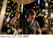 Купить «musician in headphones playing drum kit at concert», фото № 27731900, снято 18 августа 2016 г. (c) Syda Productions / Фотобанк Лори