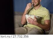 Купить «close up of man with popcorn watching tv at night», фото № 27732356, снято 26 ноября 2016 г. (c) Syda Productions / Фотобанк Лори
