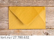 Купить «Golden envelope over  wooden background.», фото № 27780632, снято 20 октября 2018 г. (c) PantherMedia / Фотобанк Лори