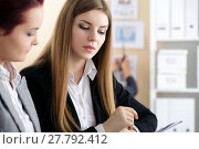 Купить «Two woman sitting at office and looking at charts», фото № 27792412, снято 26 мая 2016 г. (c) Людмила Дутко / Фотобанк Лори