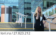 Купить «Young woman standing on the stairs and talking on a cellular phone amid business center», видеоролик № 27823212, снято 8 июля 2015 г. (c) Алексей Кузнецов / Фотобанк Лори