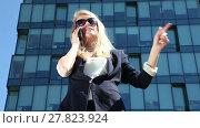 Купить «Business woman gives orders on her cell phone on the background of office building», видеоролик № 27823924, снято 8 июля 2015 г. (c) Алексей Кузнецов / Фотобанк Лори