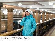 Купить «Woman talking on phone in Moscow metro in Russia», фото № 27826544, снято 11 февраля 2018 г. (c) Володина Ольга / Фотобанк Лори