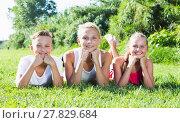 Купить «Girl with two friends resting on grass», фото № 27829684, снято 27 июля 2017 г. (c) Яков Филимонов / Фотобанк Лори