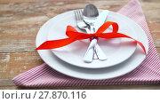 Купить «cutlery tied with red ribbon on plate», видеоролик № 27870116, снято 10 февраля 2018 г. (c) Syda Productions / Фотобанк Лори