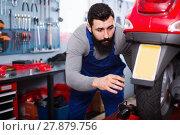 Купить «Male worker fixing failed scooter in workshop», фото № 27879756, снято 25 сентября 2018 г. (c) Яков Филимонов / Фотобанк Лори
