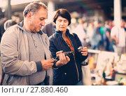 Купить «Happy mature spouses buying retro handicrafts on flea market», фото № 27880460, снято 23 октября 2017 г. (c) Яков Филимонов / Фотобанк Лори