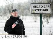 """Купить «Мужчина курит сигарету возле таблички """"Место для курения"""" зимним днём», эксклюзивное фото № 27909964, снято 23 января 2018 г. (c) Игорь Низов / Фотобанк Лори"""