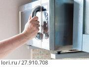 Купить «hand closes microwave oven for cooking food», фото № 27910708, снято 24 февраля 2018 г. (c) PantherMedia / Фотобанк Лори