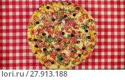 Купить «Rotating pizza with cheese, tomatoes and olives on the red tablecloth», видеоролик № 27913188, снято 13 марта 2016 г. (c) Алексей Кузнецов / Фотобанк Лори