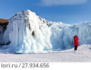 Купить «Baikal Lake in winter sunny day. Olkhon Island. An unknown tourist in a red jacket takes pictures of beautiful icy rocks on a mobile phone», фото № 27934656, снято 11 февраля 2018 г. (c) Виктория Катьянова / Фотобанк Лори