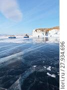 Купить «Baikal Lake in winter sunny afternoon. Tourists travel on the ice of a frozen lake on boats on air cushions around the island of Olkhon», фото № 27934696, снято 11 февраля 2018 г. (c) Виктория Катьянова / Фотобанк Лори