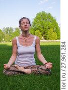 Купить «Young woman sitting in yoga pose meditation outdoors», фото № 27961284, снято 23 апреля 2019 г. (c) PantherMedia / Фотобанк Лори
