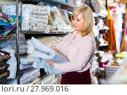 Купить «Positive mature woman choosing cotton bedcover in the textile shop», фото № 27969016, снято 17 января 2018 г. (c) Яков Филимонов / Фотобанк Лори