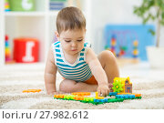 Купить «toddler boy playing indoors with developmental toy sitting on soft carpet», фото № 27982612, снято 16 декабря 2018 г. (c) Оксана Кузьмина / Фотобанк Лори