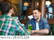 Купить «male friends drinking green beer at bar or pub», фото № 28013224, снято 22 апреля 2015 г. (c) Syda Productions / Фотобанк Лори