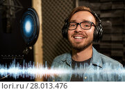 Купить «man with headphones singing at recording studio», фото № 28013476, снято 18 августа 2016 г. (c) Syda Productions / Фотобанк Лори