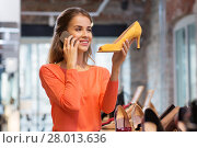 Купить «young woman calling on smartphone at shoe store», фото № 28013636, снято 22 сентября 2017 г. (c) Syda Productions / Фотобанк Лори