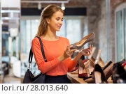 Купить «happy young woman choosing shoes at store», фото № 28013640, снято 22 сентября 2017 г. (c) Syda Productions / Фотобанк Лори