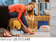Купить «young woman trying high heeled shoes at store», фото № 28013648, снято 22 сентября 2017 г. (c) Syda Productions / Фотобанк Лори