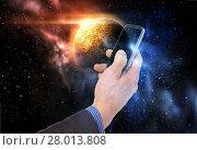 Купить «hand holding smartphone over planet in space», фото № 28013808, снято 17 ноября 2012 г. (c) Syda Productions / Фотобанк Лори