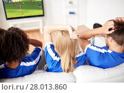 football fans watching soccer on tv at home. Стоковое фото, фотограф Syda Productions / Фотобанк Лори
