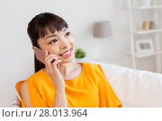Купить «happy asian woman calling on smartphone at home», фото № 28013964, снято 9 марта 2016 г. (c) Syda Productions / Фотобанк Лори