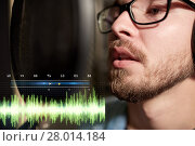 Купить «man with headphones singing at recording studio», фото № 28014184, снято 18 августа 2016 г. (c) Syda Productions / Фотобанк Лори