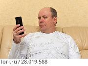 Мужчина держит телефон (2018 год). Редакционное фото, фотограф Юрий Морозов / Фотобанк Лори