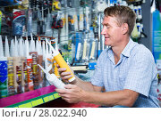 Купить «Cheerful man customer picking sealing component», фото № 28022940, снято 22 мая 2019 г. (c) Яков Филимонов / Фотобанк Лори