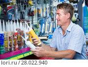 Купить «Cheerful man customer picking sealing component», фото № 28022940, снято 8 июля 2020 г. (c) Яков Филимонов / Фотобанк Лори