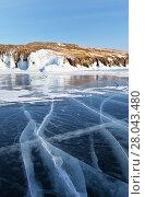 Купить «Winter landscape of the frozen Baikal Lake in February sunny afternoon. Blue clear ice with lines of cracks and icy rocky shore of Olkhon Island», фото № 28043480, снято 11 февраля 2018 г. (c) Виктория Катьянова / Фотобанк Лори