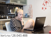 Купить «Adult woman in her casual home clothing working and studying remotely from her small flat late at night.», фото № 28043488, снято 9 июля 2020 г. (c) Matej Kastelic / Фотобанк Лори