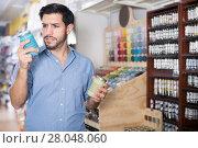 Купить «Man closely reading instruction on paint», фото № 28048060, снято 13 сентября 2017 г. (c) Яков Филимонов / Фотобанк Лори
