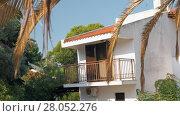 Купить «House with balcony among green trees», видеоролик № 28052276, снято 18 июля 2019 г. (c) Данил Руденко / Фотобанк Лори
