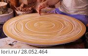 Купить «Potter drawing a decorative circular panel on a spinning wheel close-up», видеоролик № 28052464, снято 23 марта 2016 г. (c) Алексей Кузнецов / Фотобанк Лори