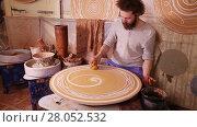 Купить «Potter creating a decorative circular panel on a spinning wheel», видеоролик № 28052532, снято 24 марта 2016 г. (c) Алексей Кузнецов / Фотобанк Лори