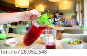 Купить «Teen pours fruit mint lemonade into glass in cafe», видеоролик № 28052548, снято 24 июля 2017 г. (c) Володина Ольга / Фотобанк Лори