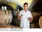 Купить «friendly man checking ageing process of red wine», фото № 28052872, снято 21 сентября 2016 г. (c) Яков Филимонов / Фотобанк Лори